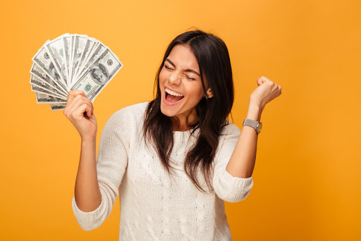 a woman holding a handful of fanned-out, hundred-dollar bills and pumping her fist in victory